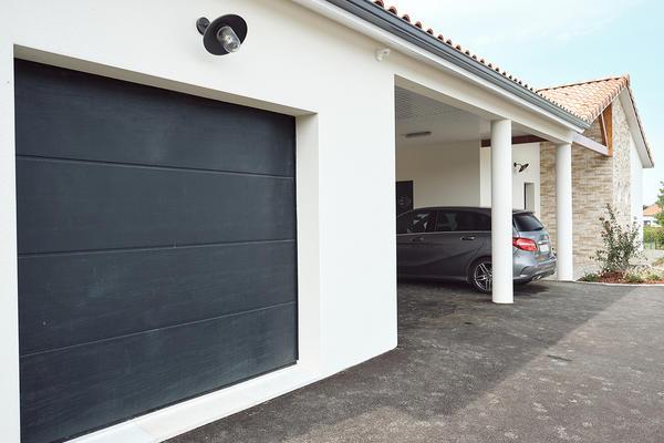 Porte de garage sectionnelle anthracite Maison contemporaine avec parement pierre - Maison neuve Constructeur Mètre Carré
