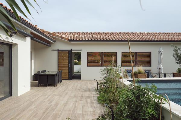 Terrasse carrelé et piscine semi-enterrée - Maison contemporaine avec parement pierre - Maison neuve Constructeur Mètre Carré