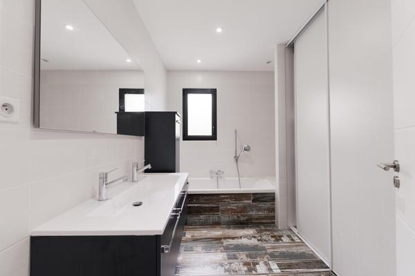 Salle de bain avec meuble double vasque, baignoire et rangement intégré